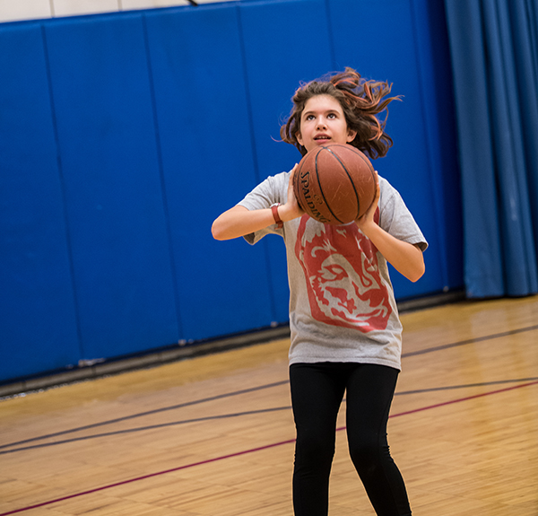 9/10s child shoots basketball
