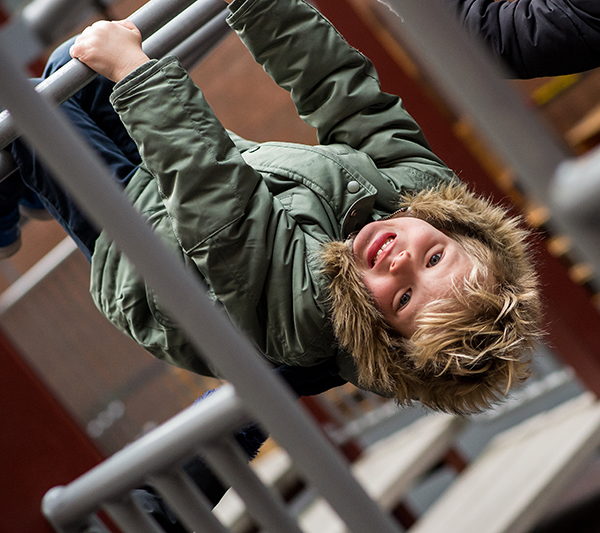 Child hanging upside down from jungle gym
