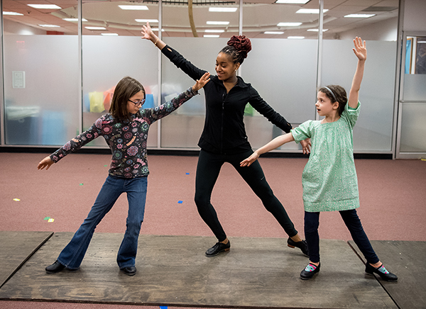 Teacher dancing with two students in movement class