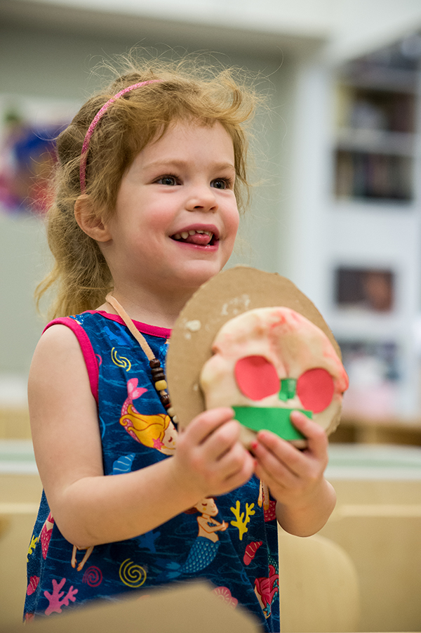 Child smiles while holding artwork
