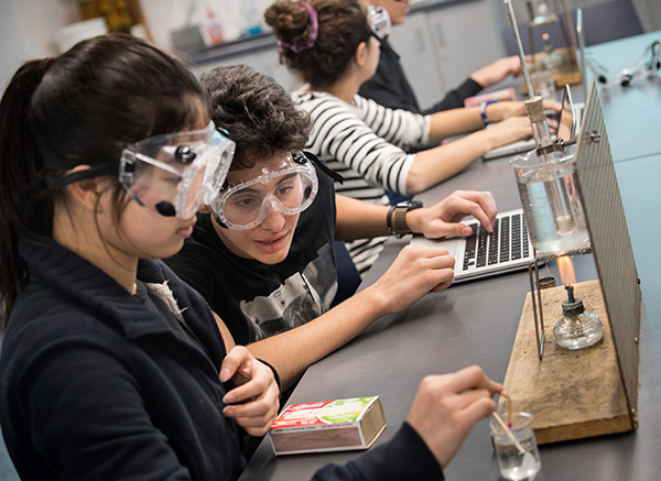 11/12s students conduct science experiment in goggles