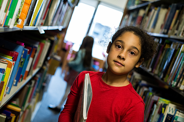 8/9s student in between library bookshelves