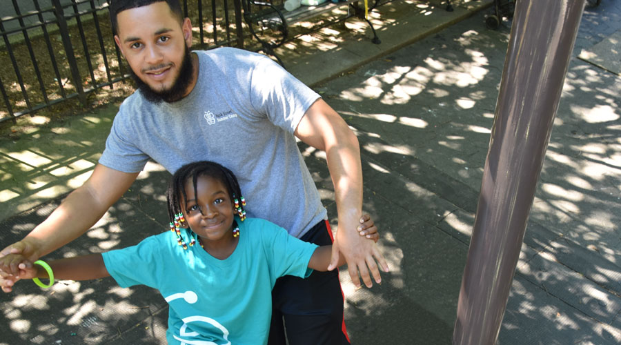 A counselor of color smiles and plays with a young camper of color