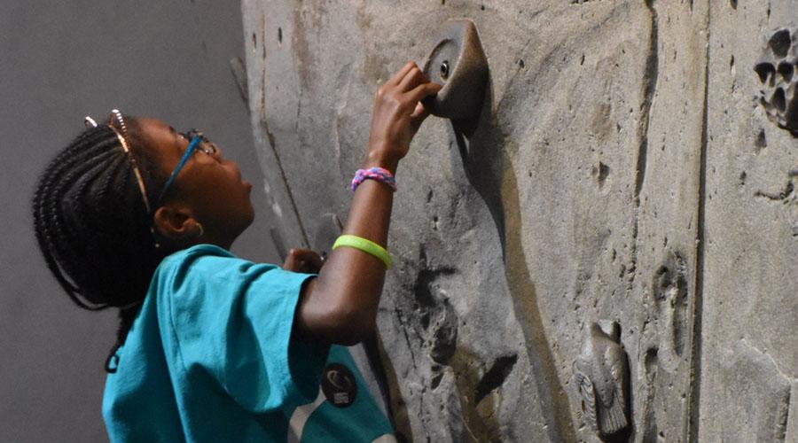 An older camper climbs a rock