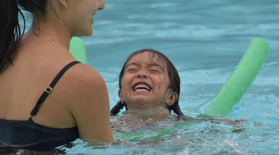 A young camper smiles and she swims toward a counselor in the pool