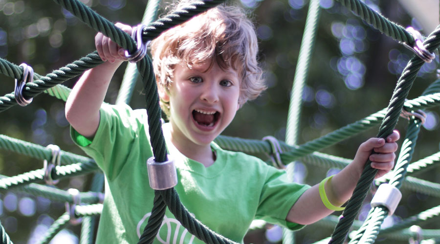 A young camper smiles as he climbs through some ropes