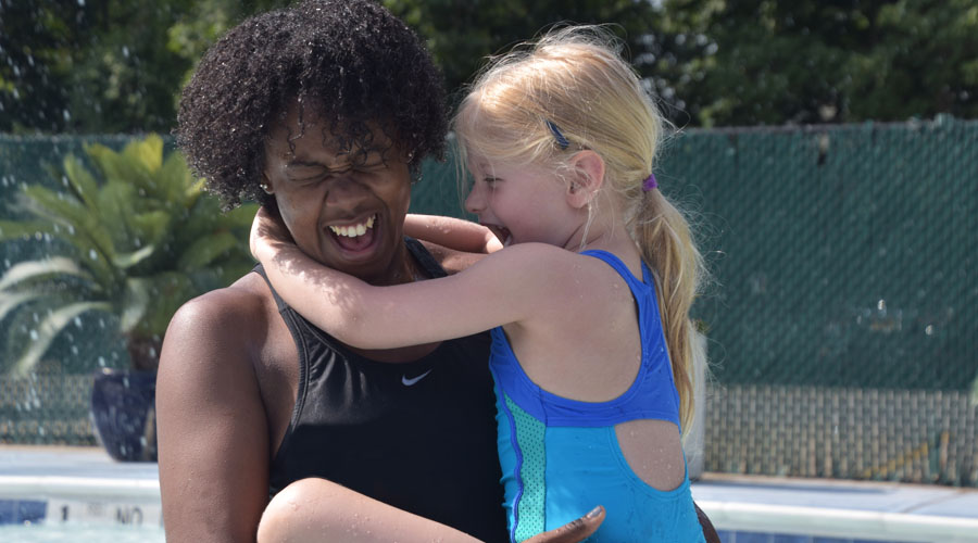 A counselor of color holds a camper laughing as the camper smiles