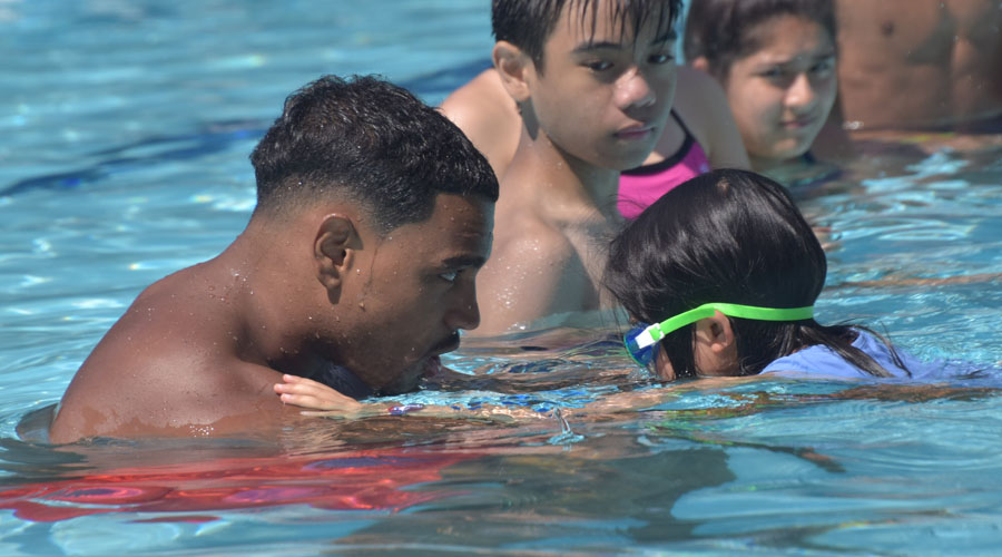 A counselor and camper face one another in the water as they focus on building skills in the pool