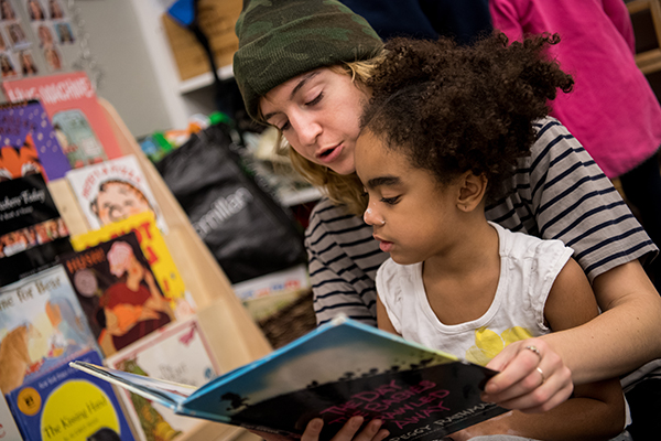 Child reading with teacher