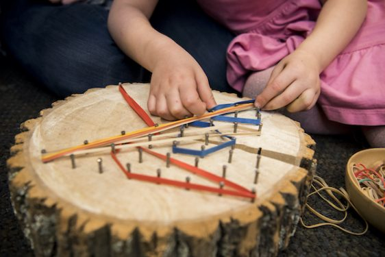 Child makes rubber band design on top of tree log