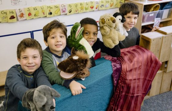 Four kids holding puppets