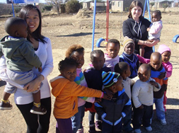 Emily Soong and Laura Zellerbach '11 with children in a South African crèche.