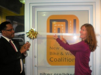 Montclair Township Manager Marc Dashield applauds as Cyndi Steiner, executive director of the New Jersey Bike & Walk Coalition, cuts the ribbon to open the new Montclair Bike Depot.