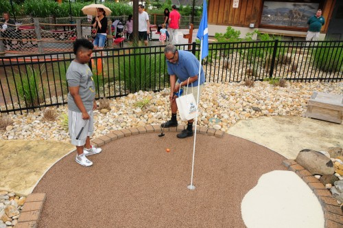 Big Brother Big Sisters: Juan Lopez, a mentor with Big Brothers Big Sisters of Essex, Hudson & Union Counties, teachers his Little Brother and mentee, Carlos Reyes, how to sink a hole in one at the Turtle Back Zoo's Mini Golf Classic on Saturday, June 20.  The first annual event raised over $100,000 to support the Zoo's Education Center.