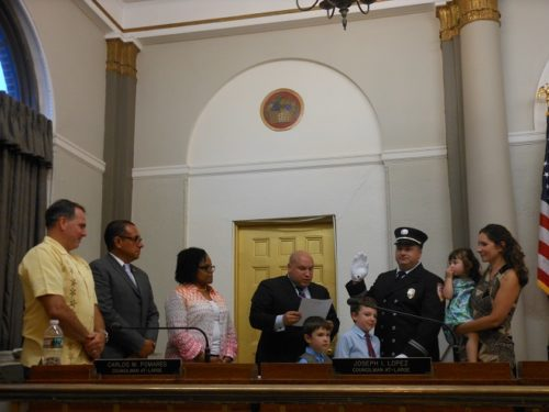 Bloomfield Mayor Michael Venezia (center) swears in Fred Mamay as a new fire department captain, with council members and Mamay's family looking on.