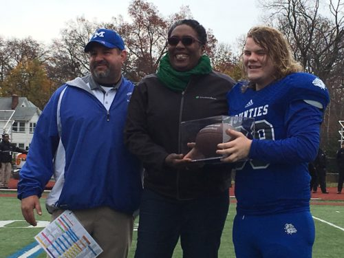 Senior defensive lineman Liam Devine-Carter, right  receives Montclair's Most Valuable Player award following the Mounties' 30-23 win over Bloomfield Thursday.