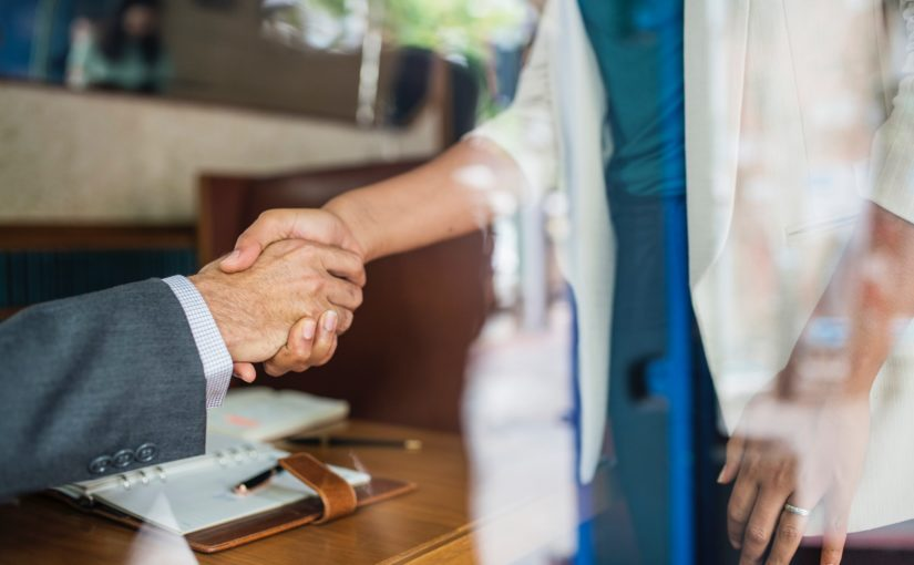 Business people shaking hands. Photo by rawpixel on Unsplash