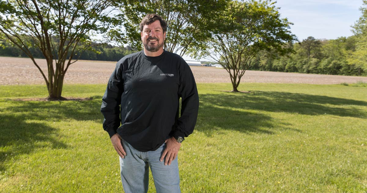 Land surveyor Russell Hammond standing in yard with farm land in the background