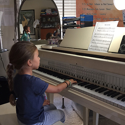 young girl learning to play piano