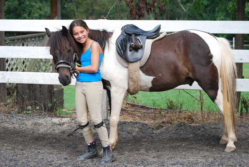 young girl smiling with friendly horse at summer camp