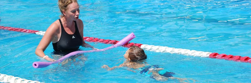 kids learning to swim at summer camp