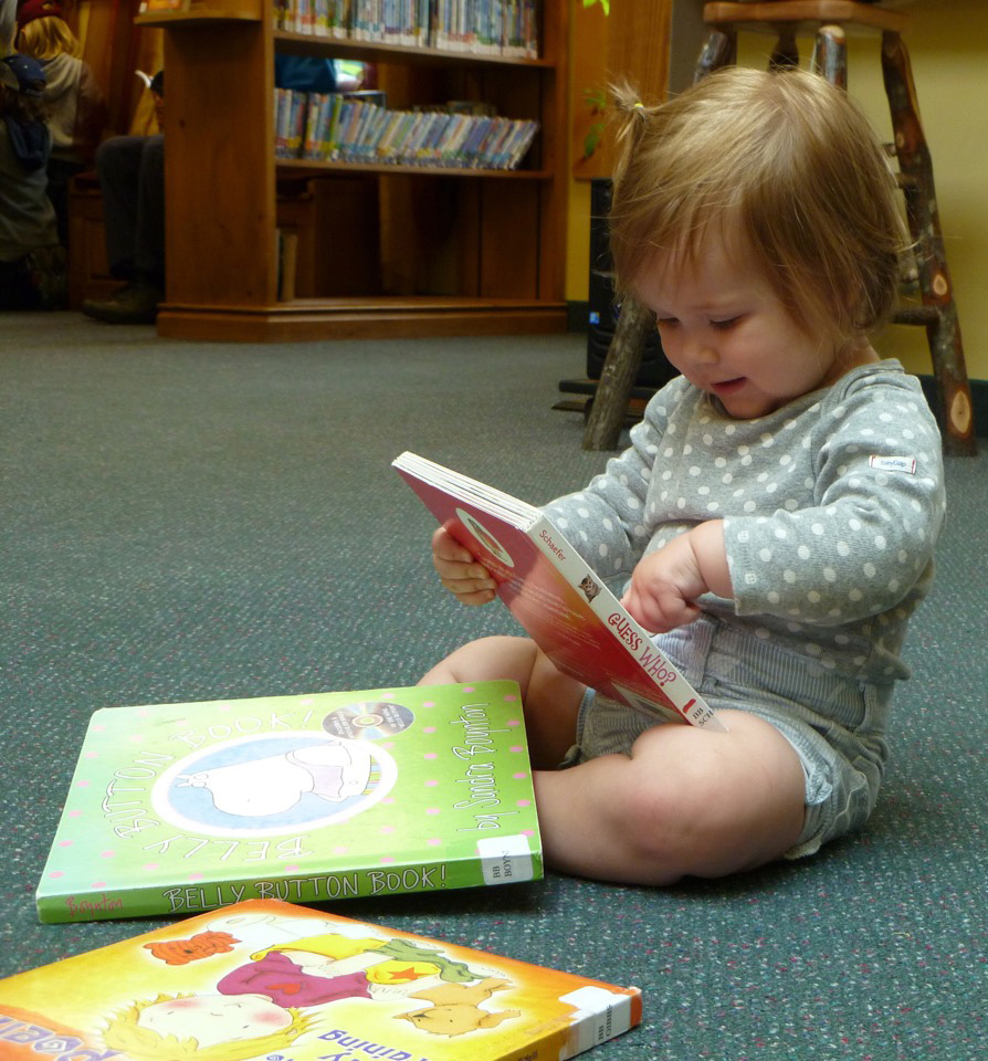 A young child reading a book at the Dwight Branch