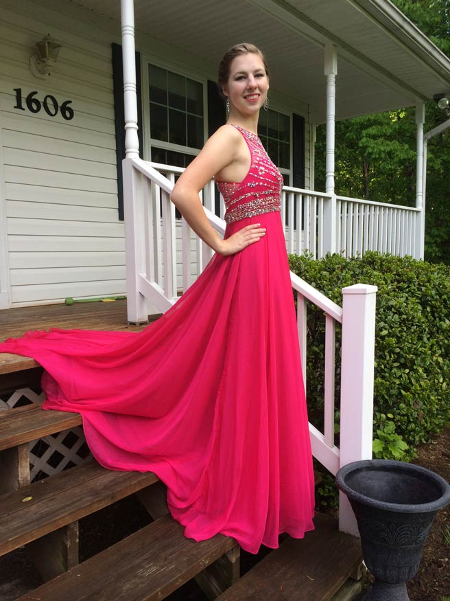 young girl in red prom dress from side