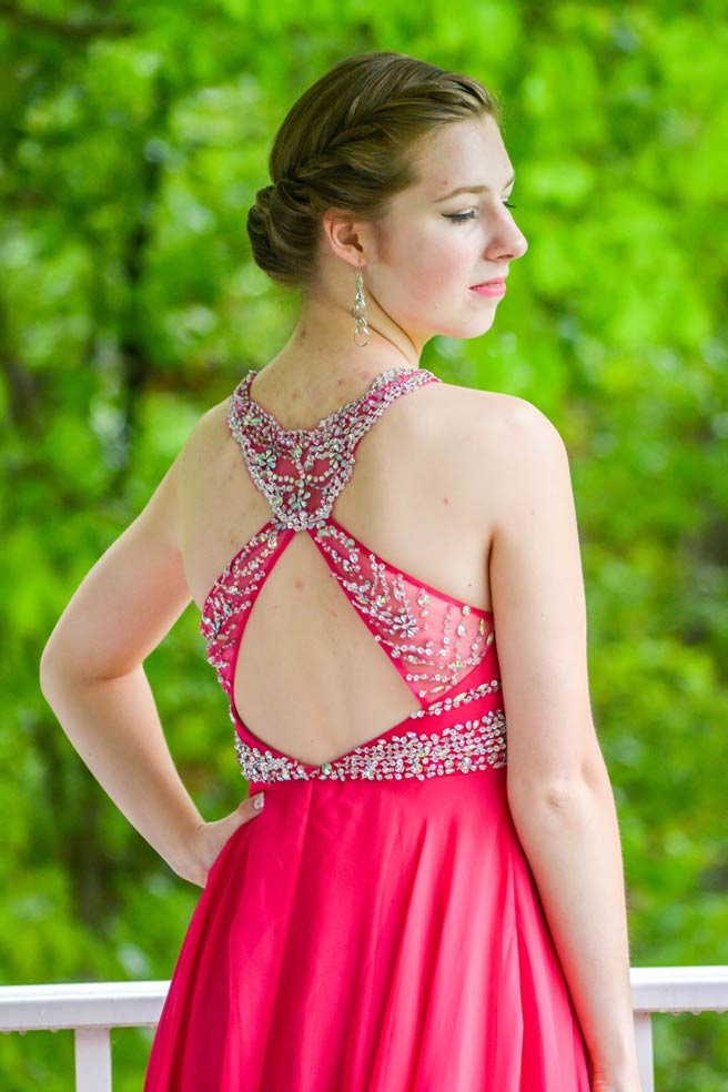 young girl in red prom dress from back