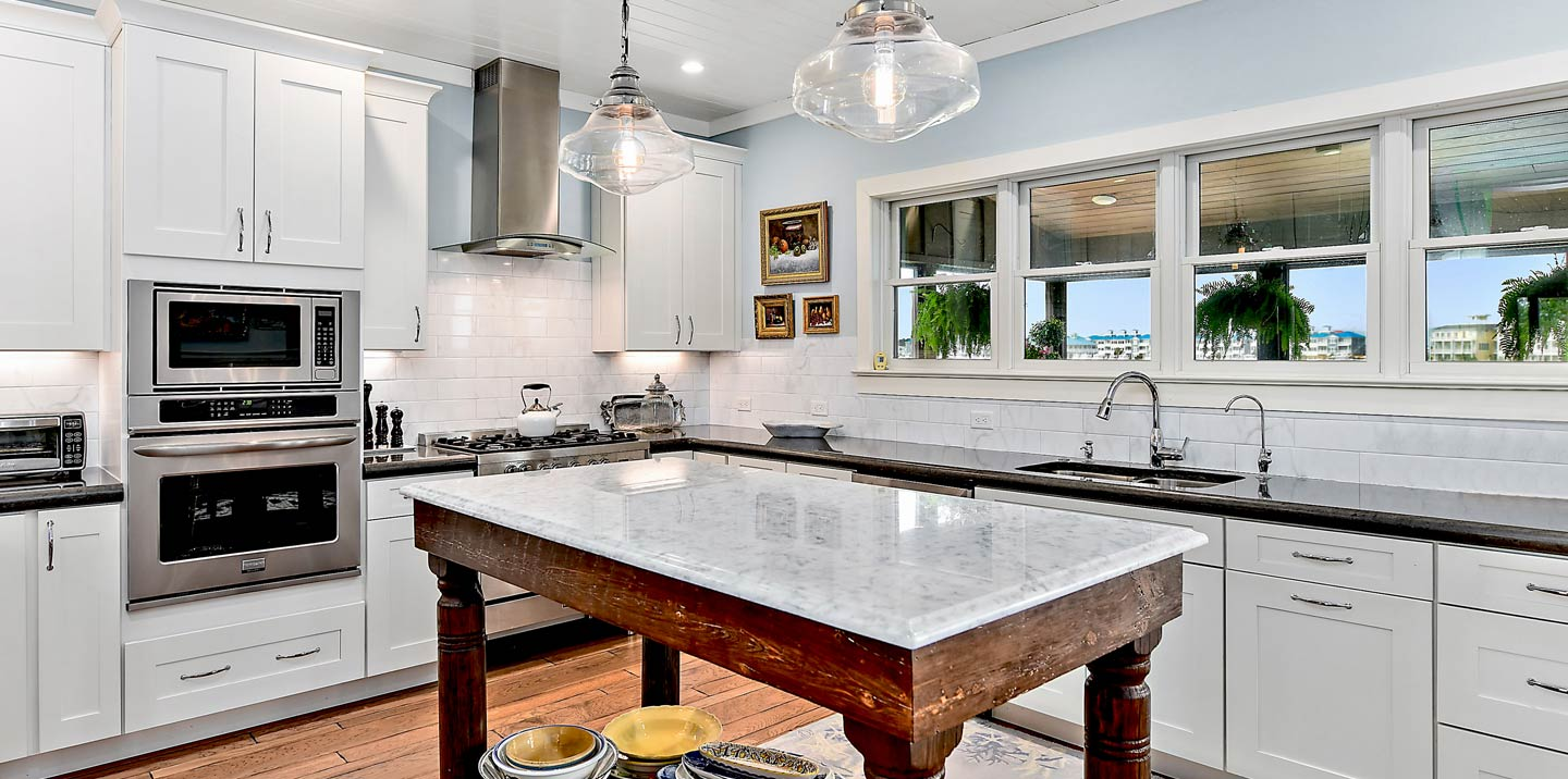 Modern custom kitchen with white shaker style cabinets and a reclaimed table as the kitchen island.