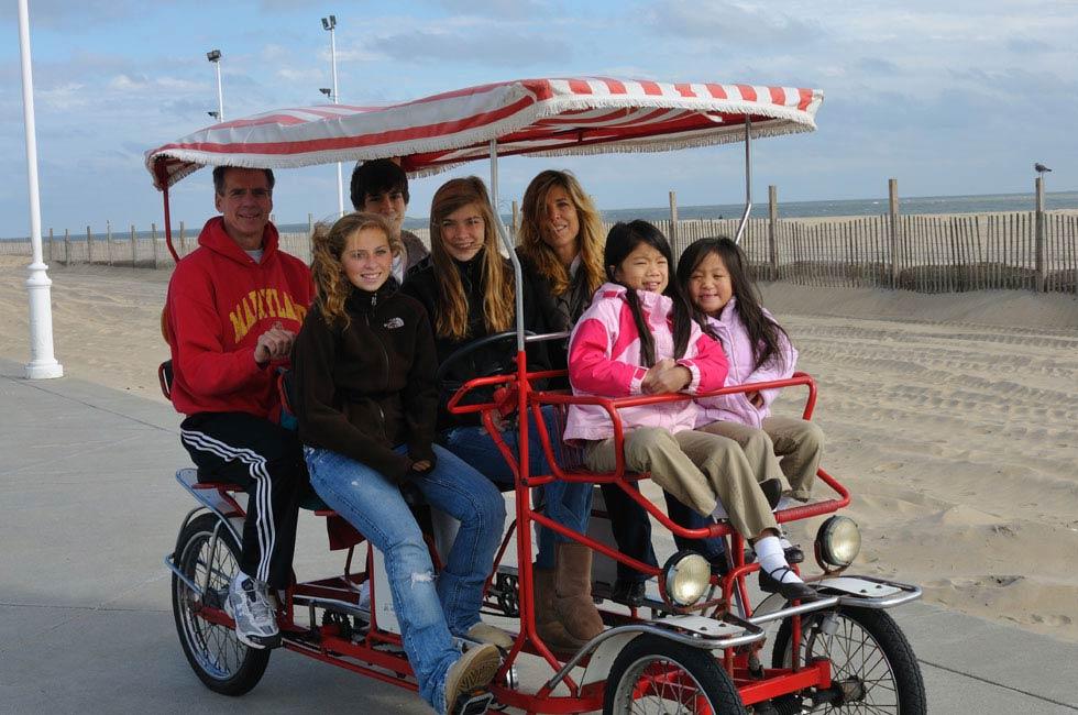 Smiling family rising on a Surrey bike on Ocean City MD Boardwalk