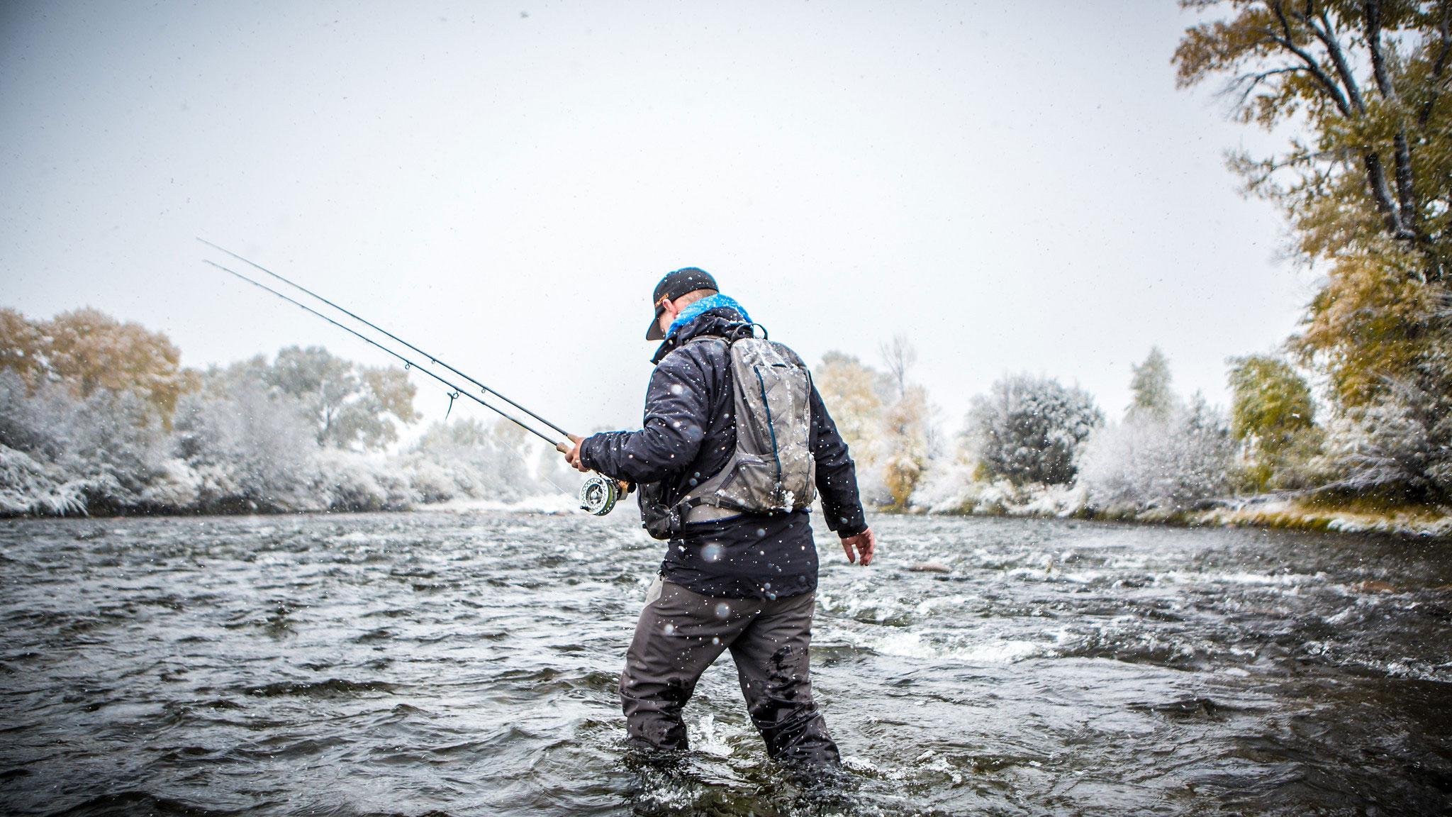 Fisherman walking through stream during snowy season