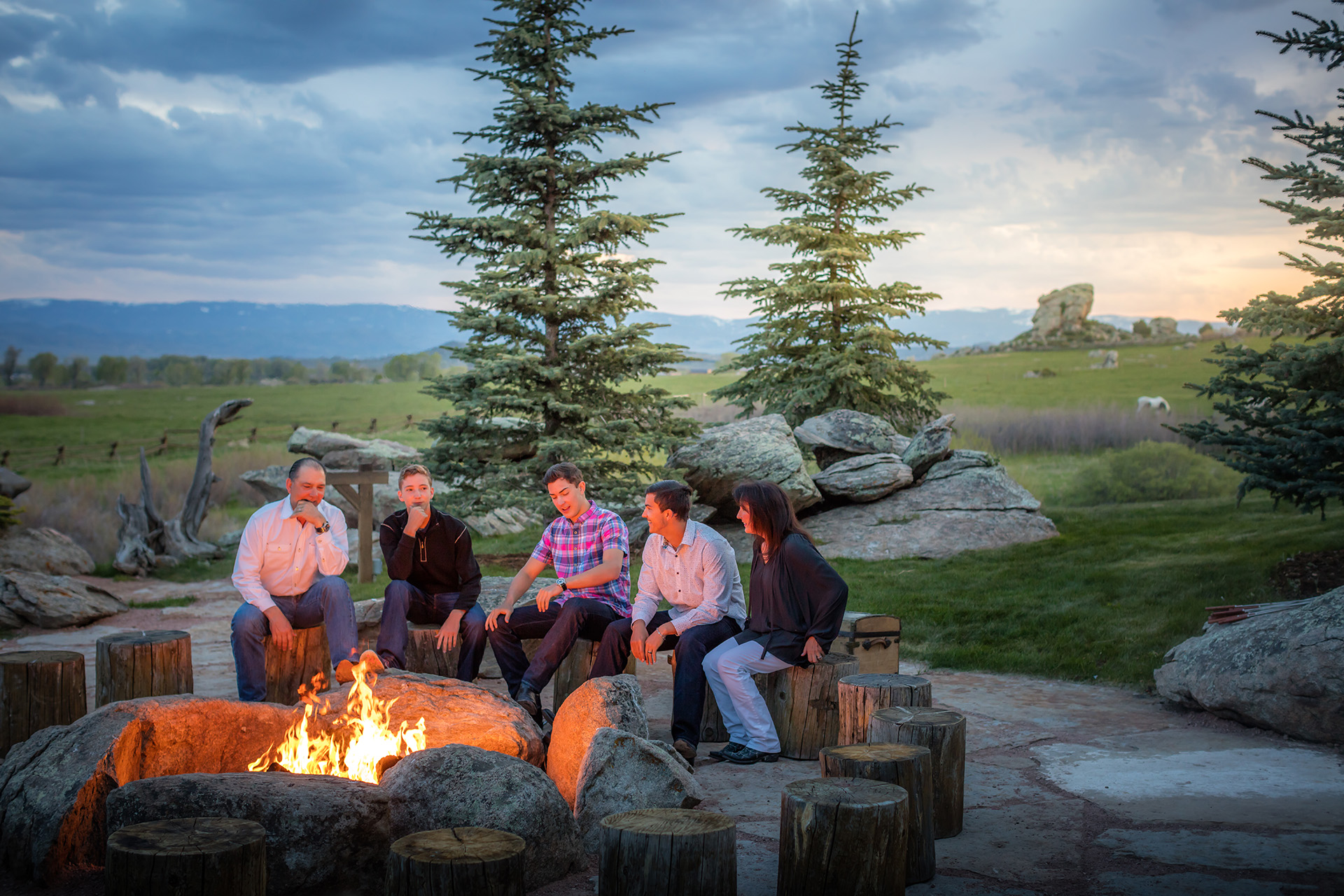 Family of five sitting around a campfire at dusk.
