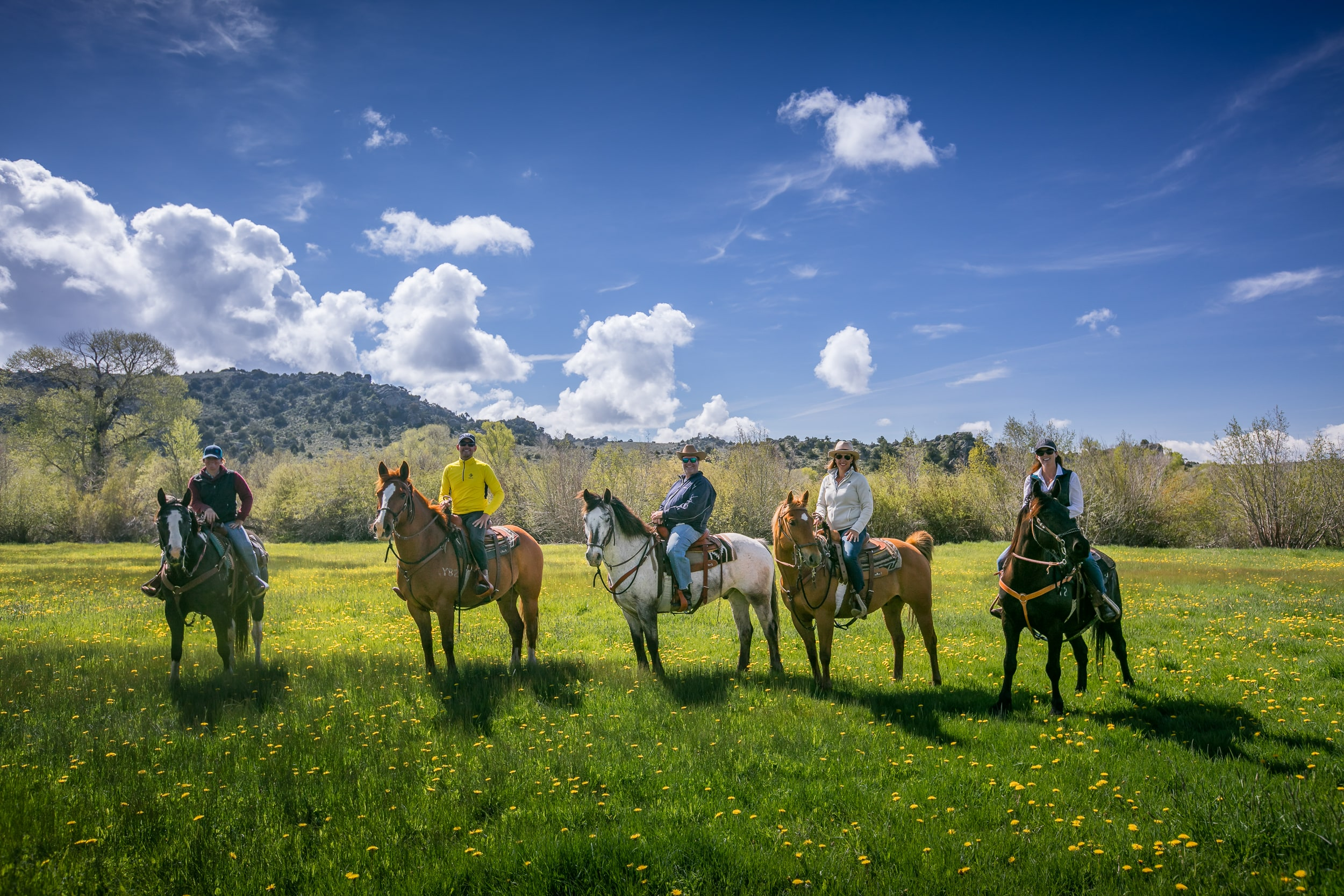 Five horse riders on a breathtaking trail at Brush Creek Luxury Ranch