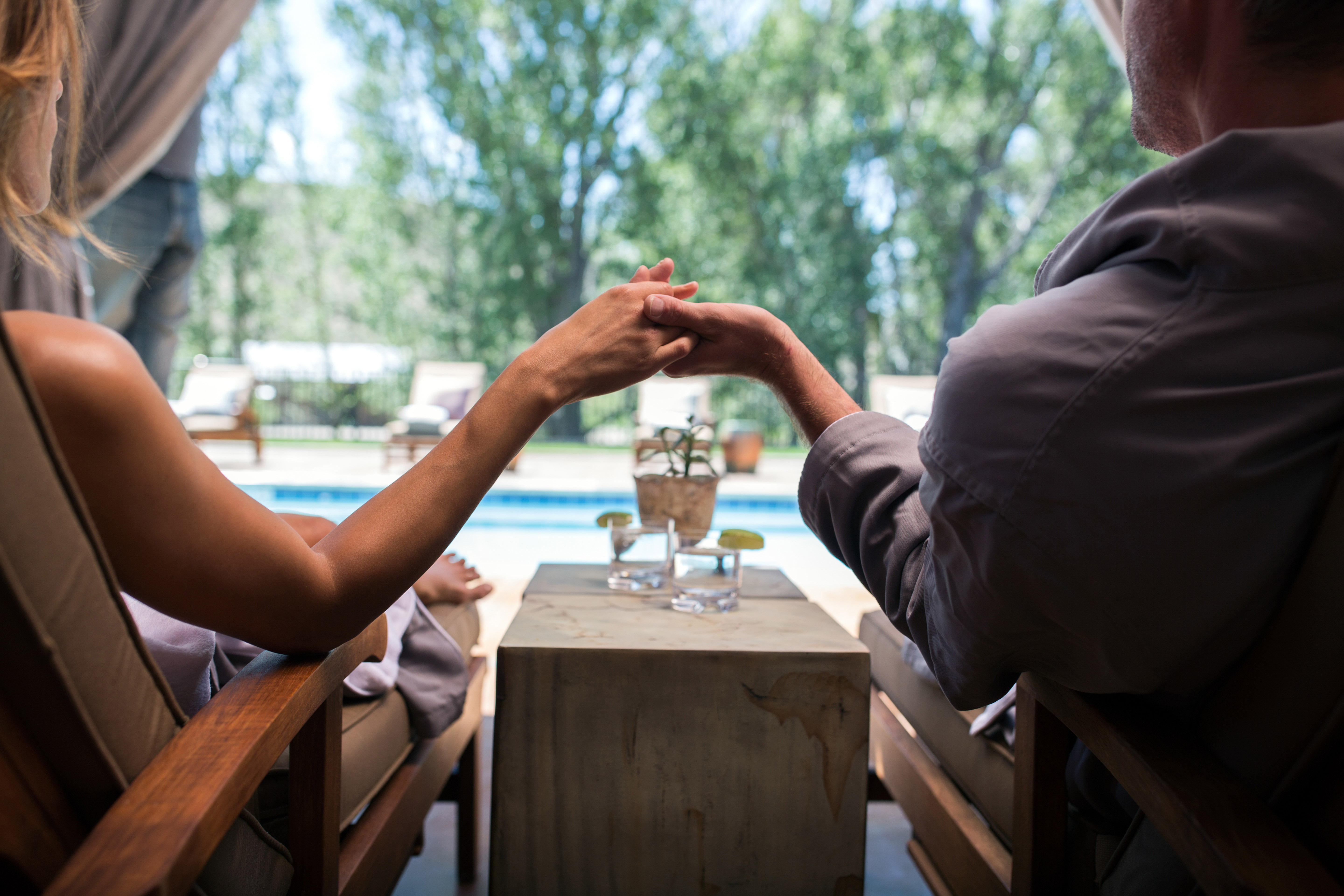 Man and woman holding hands under Magee cabana with cocktails