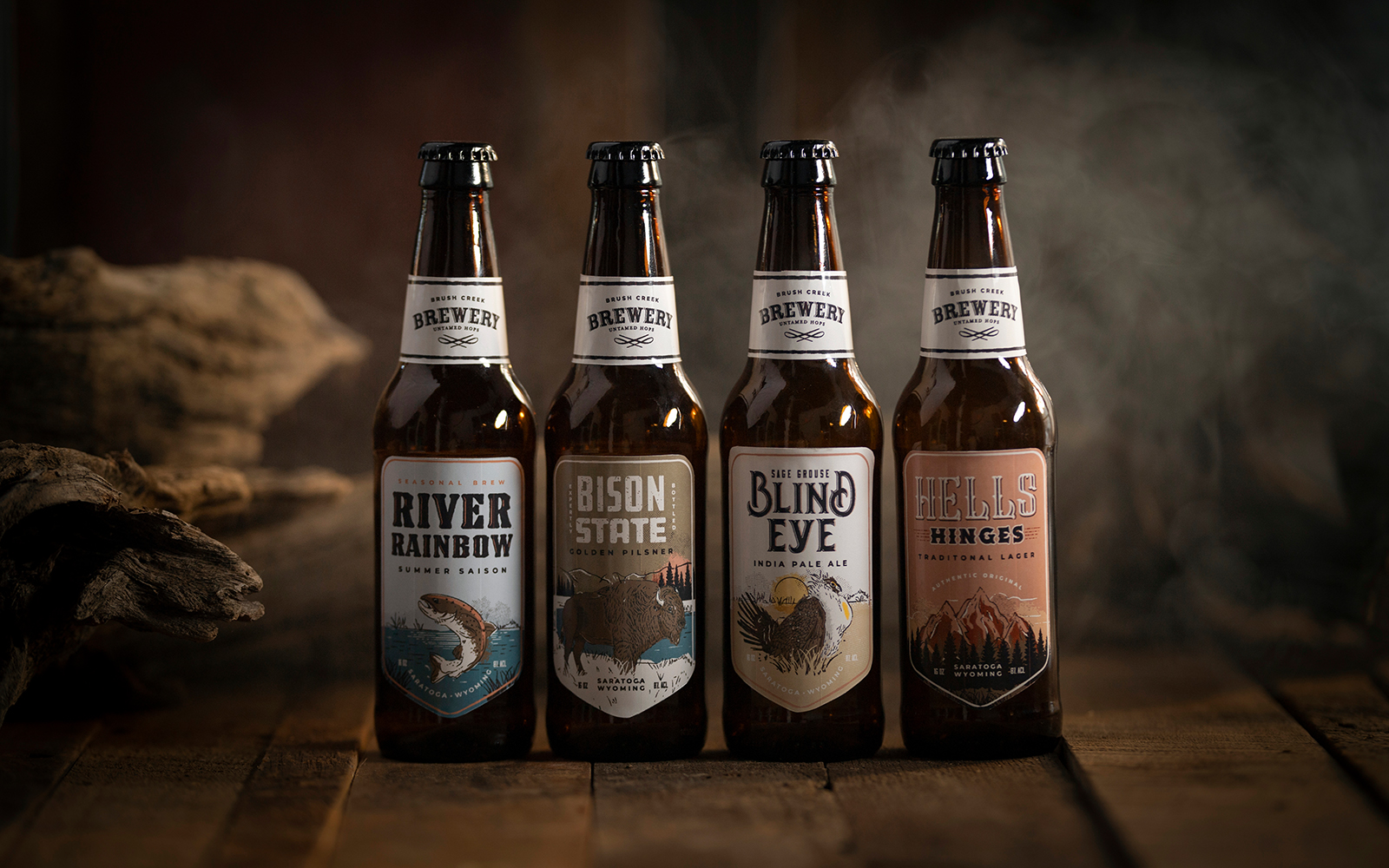 Four bottles of Brush Creek Brewery beer collection. River Rainbow, Bison State, Blind Eye, and Hells Hinges