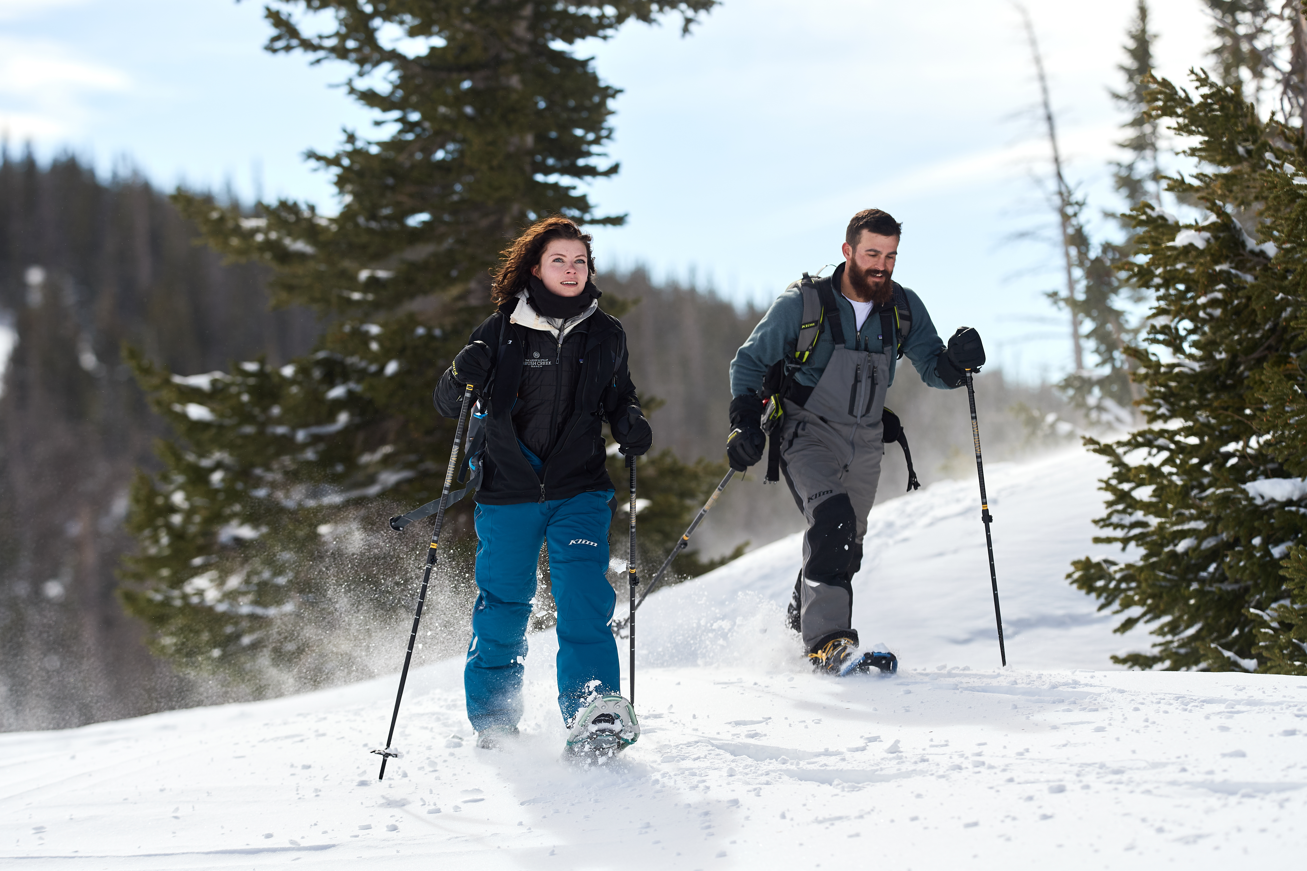 A young couple snowshoeing along the snowy trails at the Nordic Yurt around Green Mountain