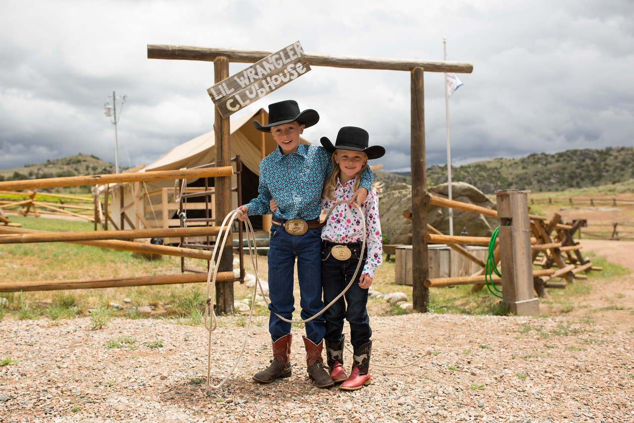 A boy and a girl holding a lasso outside of the Lil' Wranglers Clubhouse