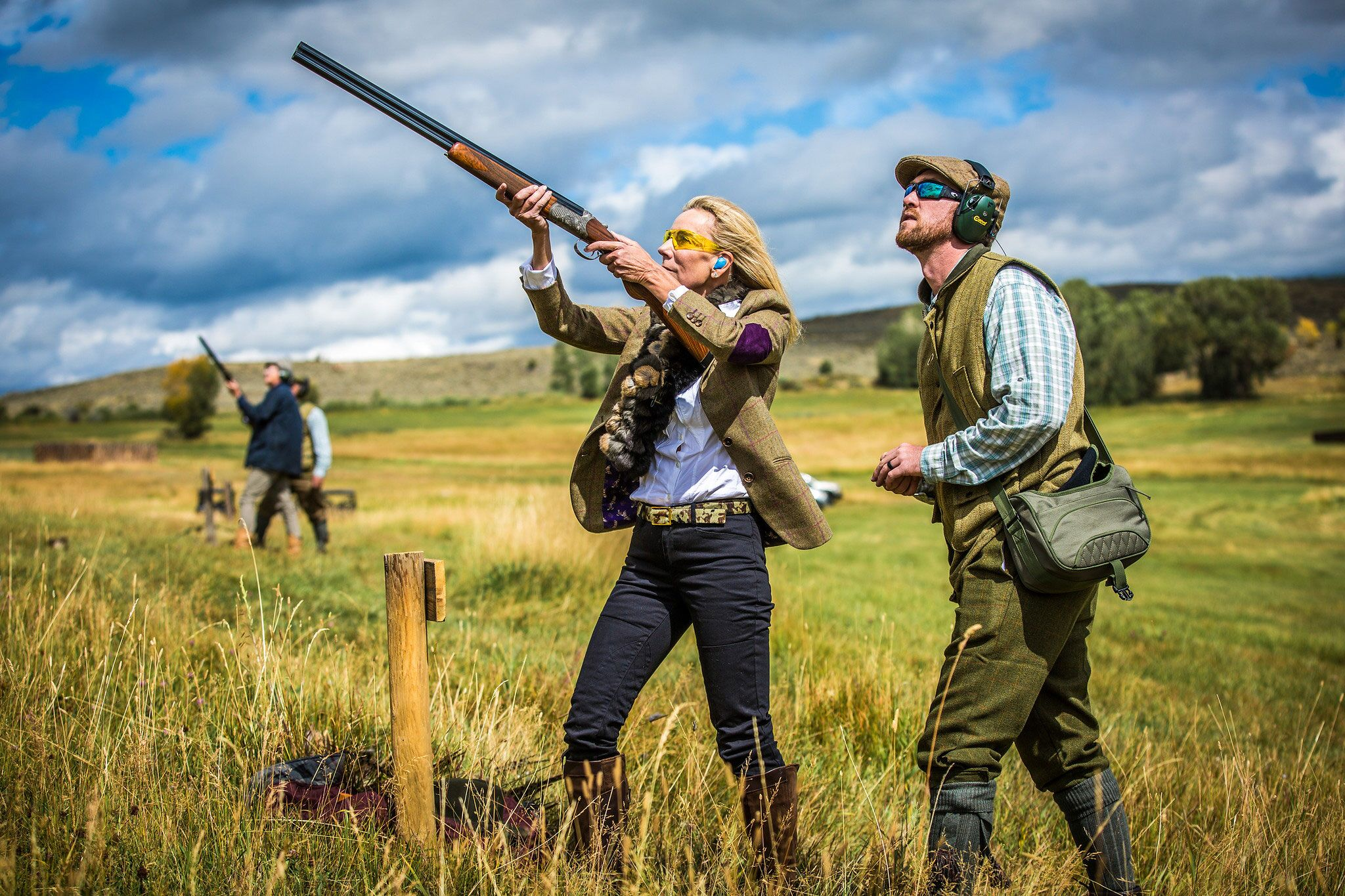 Woman wingshooting with aide from guide