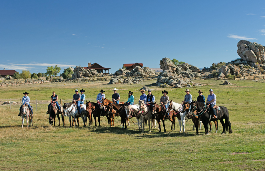 Corporate group lined up on horseback in front of The Lodge and Spa.