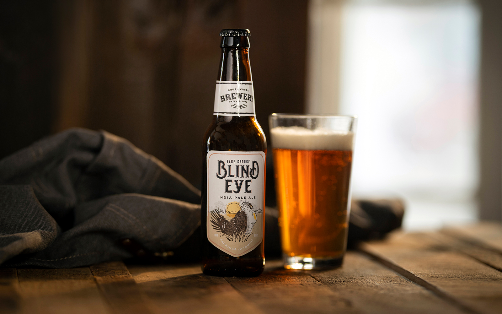A bottle and a glass of Brush Creek Brewery beer collection, Blind Eye, on top of a rustic wood table