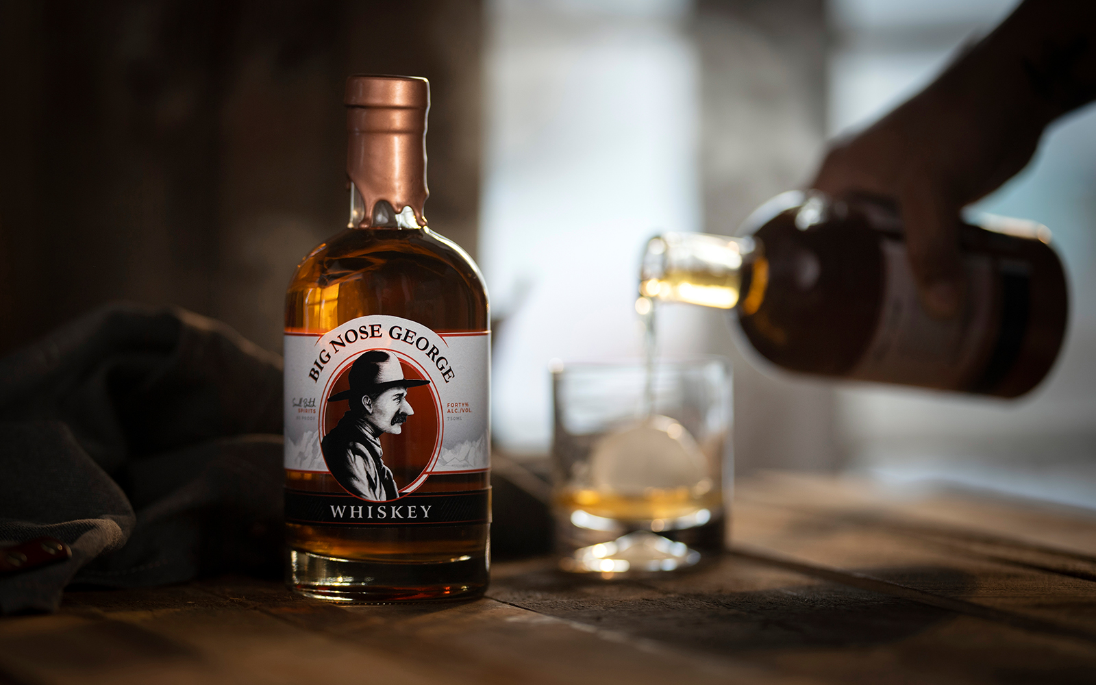 A bottle of the Big Nose George Whisky from the Brush Creek Distillery being served in a glass with ice