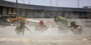 Labourers sweep dust and stones at a road construction site in Ahmedabad, India, May 3, 2016. REUTERS/Amit Dave