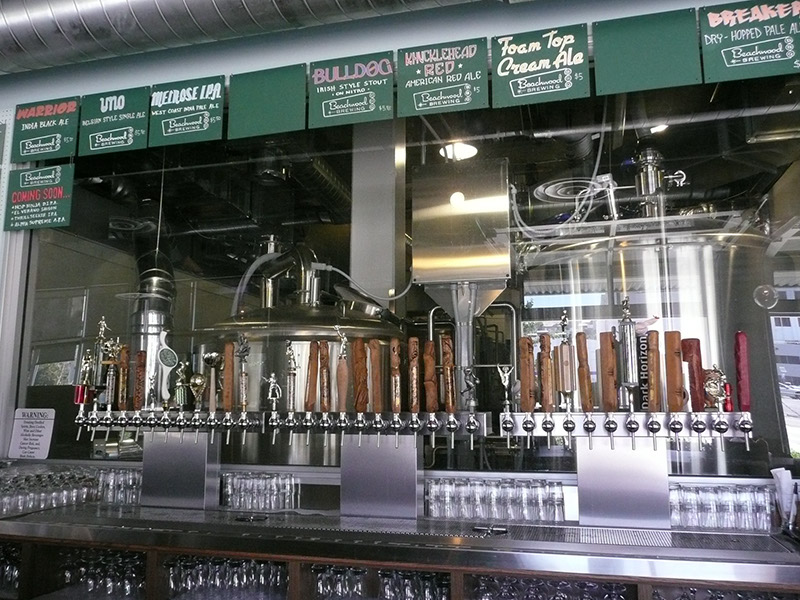 The tap handles at the bar with the brewery just visible through the glass behind