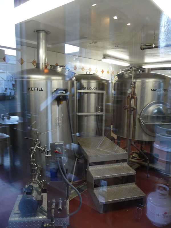 The brewing tanks seen though the glass partition