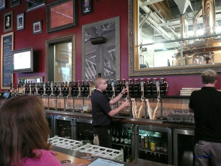 The tap handles behind the bar with a glimpse of the brewery