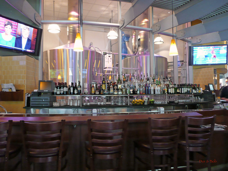 The bar with a glimpse of the brewery behind