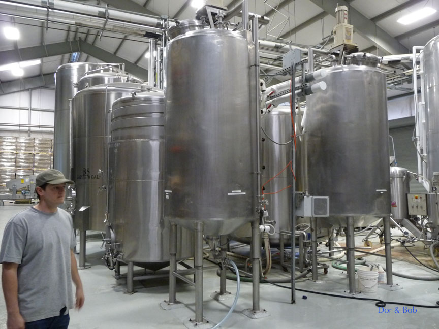 A brewer leading a tour past the fermentation tanks