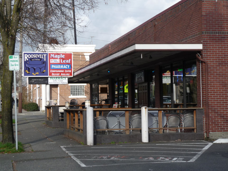 The sign and outdoor seating seen from the sidewalk