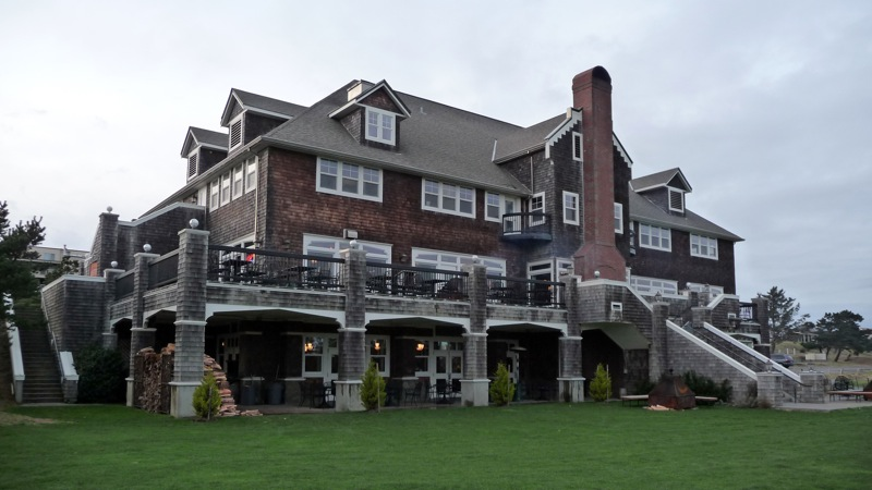 The rear of the building (seen from the golf course)  with outdoor seating on the deck and patio