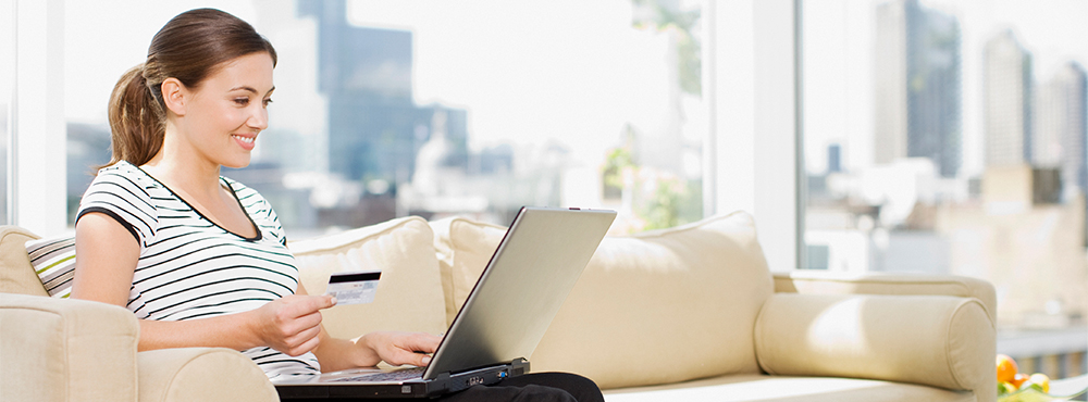 Woman on laptop sitting on couch with credit card in hand.